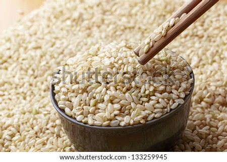 uncooked brown rice in a bowel and Chopsticks  with woody background - stock photo
