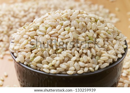 uncooked brown rice in a bowel with woody background