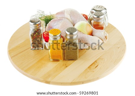 uncooked chicken drumstick and different spices on wood - stock photo