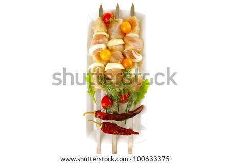 uncooked chicken shish kebab on long white - stock photo