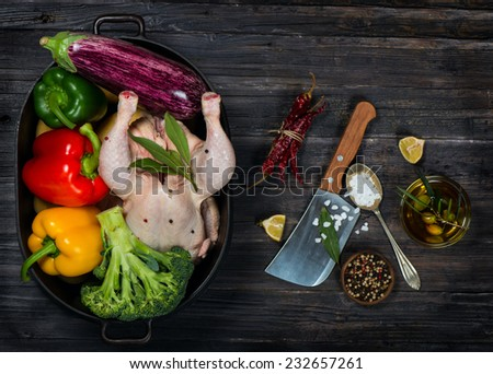 Uncooked chicken with vegetables in a black casserole on a old black wooden table  top view - stock photo
