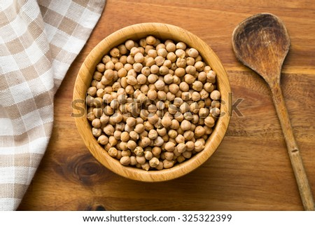 uncooked chickpeas in wooden bowl - stock photo