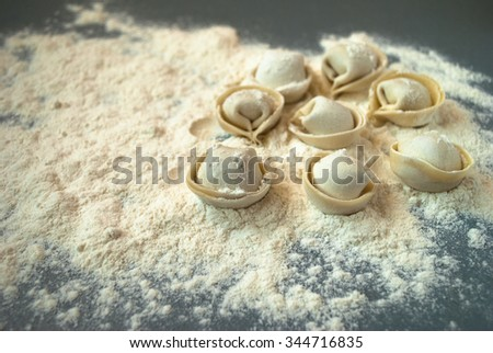 Uncooked dumplings on a blue wooden table - stock photo