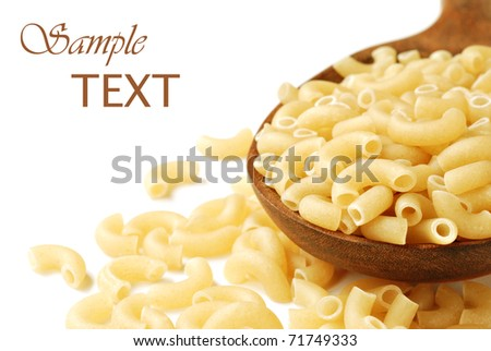Uncooked elbow macaroni spilling from wooden spoon on white background with copy space.  Macro with shallow dof. - stock photo