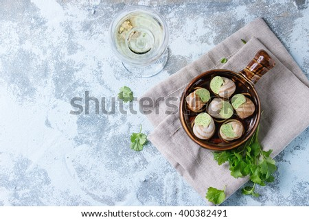 Uncooked Escargots de Bourgogne - Snails with herbs butter, gourmet dish, in traditional ceramic pan with parsley and glass of white wine over blue textured background. Top view. - stock photo
