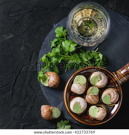 Uncooked Escargots de Bourgogne - Snails with herbs butter, in traditional ceramic pan with parsley and glass of white wine on stone slate over black textured background. Top view. Square image - stock photo