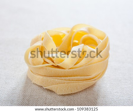 Uncooked fettuccine nest on fabric - stock photo