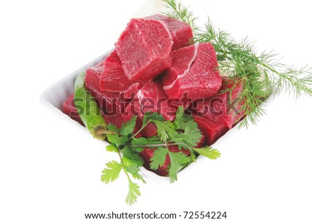 uncooked fresh beef meat chunks on white bowls with green hot peppers and vegetables isolated over white background - stock photo