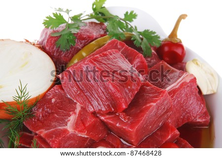 uncooked fresh beef meat chunks on white bowls with vegetables and red peppers isolated over white background - stock photo