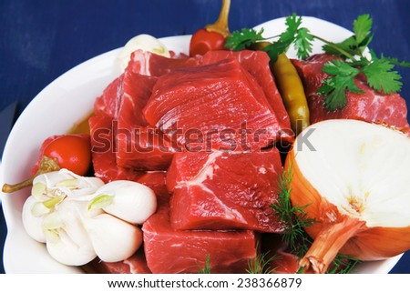 uncooked fresh beef meat chunks on white bowls with vegetables and red peppers serving on blue table with cutlery - stock photo