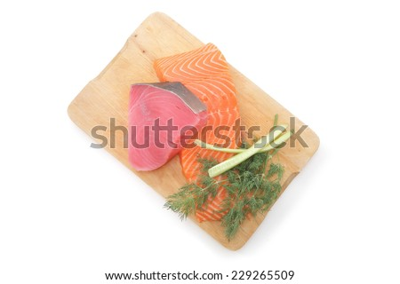 uncooked fresh salmon and red tuna fish pieces served over wooden board isolated on white background - stock photo