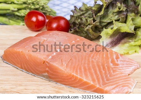 uncooked fresh salmon fish piece served over wooden board isolated on white background - stock photo