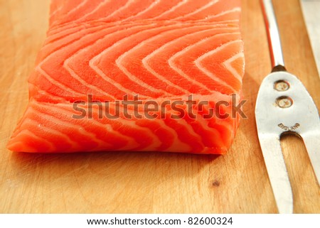 uncooked fresh salmon fish piece served over wooden board isolated on white background