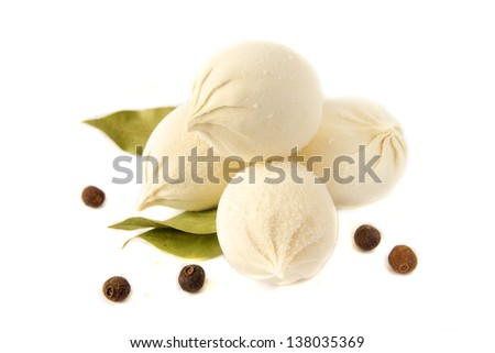 Uncooked frozen dumplings (russian traditional food - pelmeni, khinkali) with pepper and bay leaf isolated on white background close up. - stock photo