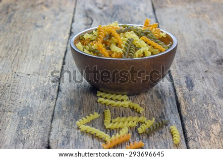 Uncooked gluten free fusilli pasta in wood blow - stock photo