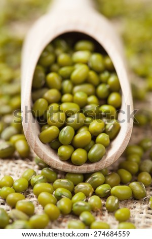 Uncooked healthy organic food green raw mung beans in wooden spoon on vintage textile background. Close up. - stock photo