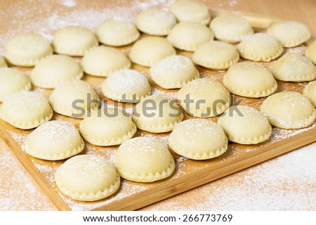 Uncooked homemade dumplings (vareniki)  with potatoes on cutting board, prepared for cooking. Selective focus - stock photo