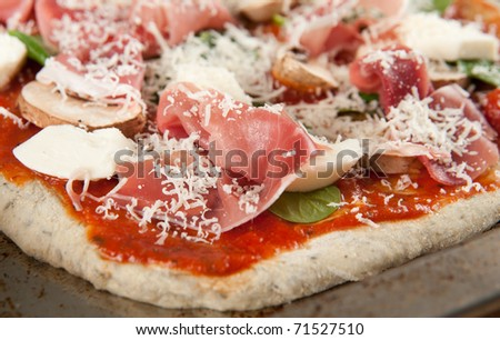 Uncooked Homemade Pizza with Mushrooms, Cured Meat, Spinach and Cheese - stock photo
