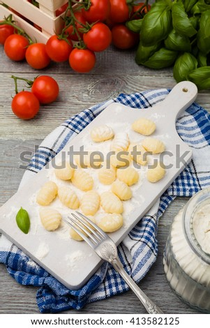 Uncooked homemade potato gnocchi with tomatoes or mushrooms with flour.  - stock photo