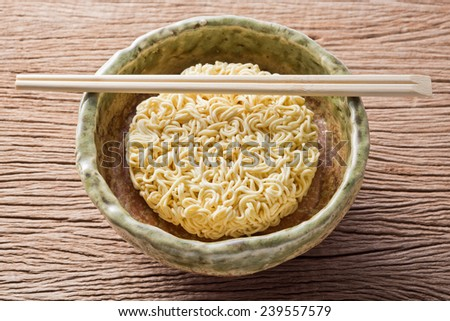 uncooked instant noodle in ceramic bowl with bamboo chopsticks - stock photo
