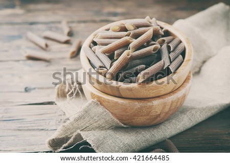 Uncooked italian buckwheat pasta on the wooden table, selective focus and toned image - stock photo