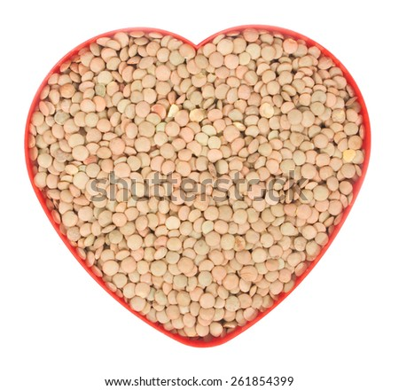 Uncooked lentil in a red heart pot isolated on white background - stock photo