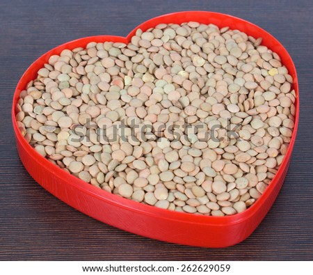 Uncooked lentil in a red heart pot on a brown surface - stock photo