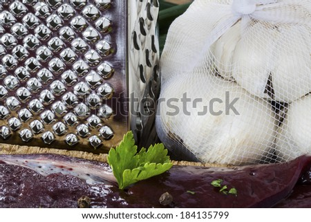uncooked liver with a grater and onions in the background, shot on a wooden surface - stock photo
