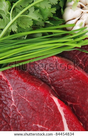uncooked meat : raw fresh beef pork fillet ready to cooking with garlic and green stuff over wood isolated over white background - stock photo