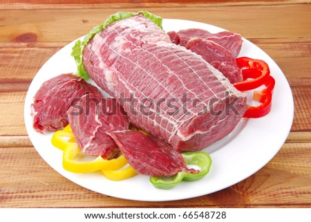 uncooked meat with vegetables on wooden table - stock photo