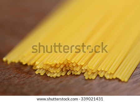 Uncooked noodles on wooden surface - stock photo