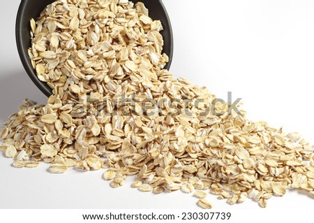 Uncooked oatmeal spilling from black bowl on a white background - stock photo