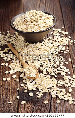 Uncooked oatmeal spilling from black bowl on a wooden background - stock photo