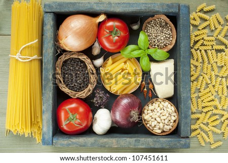 uncooked pasta and spices in wooden tray, mediterranean food ingredients - stock photo