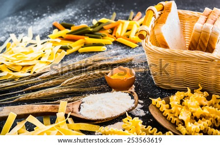 uncooked pasta, bread and other products on a black  textured table - stock photo