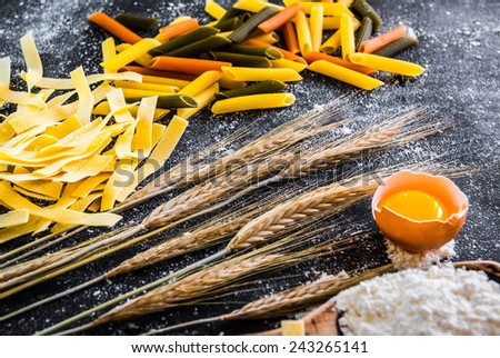 uncooked pasta, flour and other products on a black  textured table - stock photo