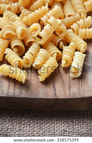 uncooked pasta on a wooden cutting board - stock photo