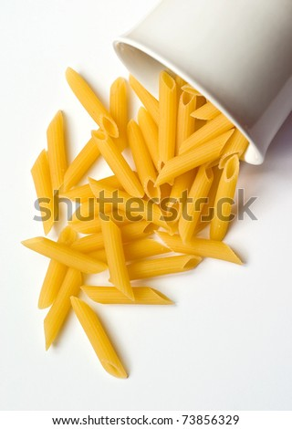 Uncooked pasta selection spilling out of a bowl - stock photo