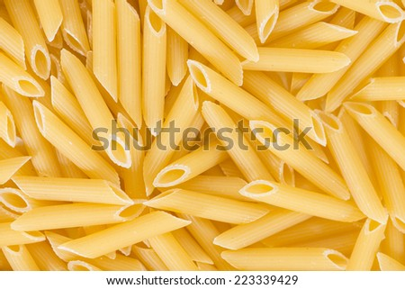 Uncooked Penne (close-up shot) for use as background image or as texture - stock photo