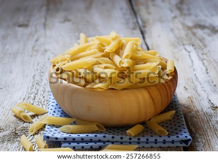 Uncooked penne pasta in wooden bowl. Selective focus - stock photo