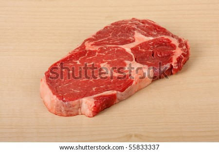 Uncooked piece of rib eye steak on a cutting board - stock photo