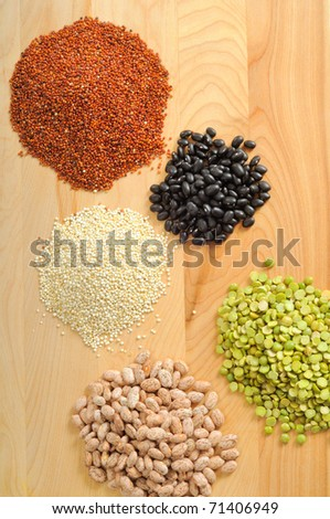 Uncooked quinoa, black beans, pinto beans, and split peas on a cutting board - stock photo