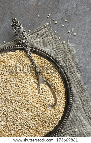 Uncooked quinoa in metal plate on wooden background - stock photo