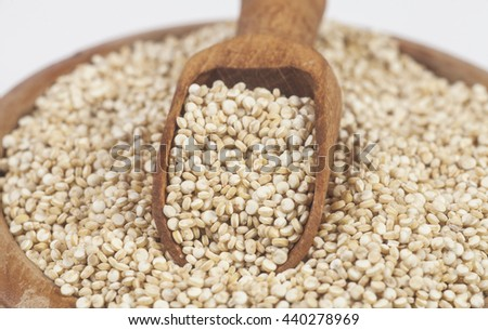 Uncooked quinoa in the wooden bowl and spoon. Macro image with selective focus. White background