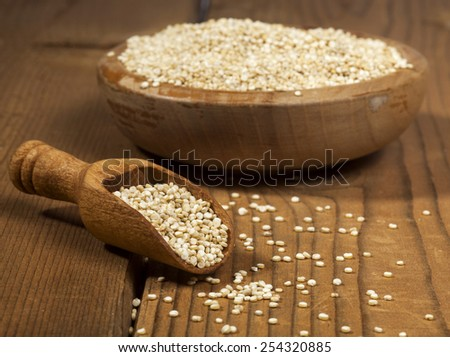 Uncooked quinoa in the wooden bowl and spoon on a wooden background. - stock photo