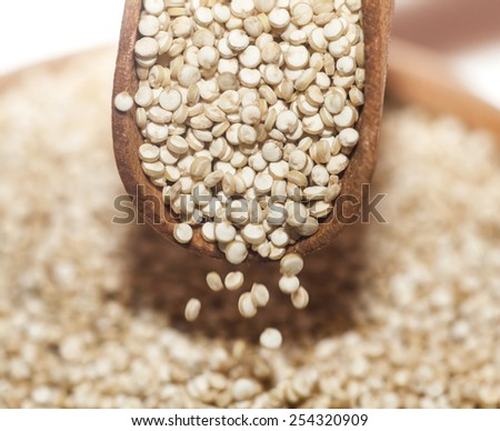 Uncooked quinoa pouring from wooden spoon. Macro image with selective focus. - stock photo