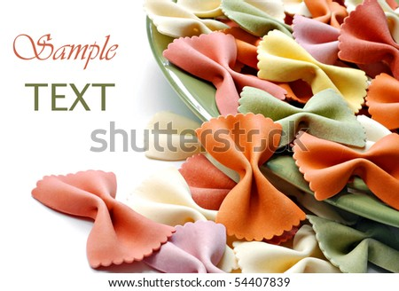 Uncooked rainbow farfalle pasta spilling from plate on white background with copy space.  Macro with shallow dof. - stock photo