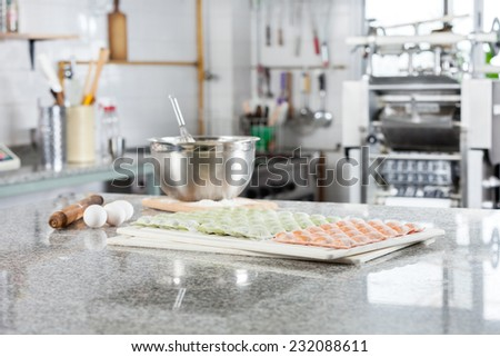 Uncooked ravioli pasta on cutting board with ingredients at countertop in commercial kitchen - stock photo