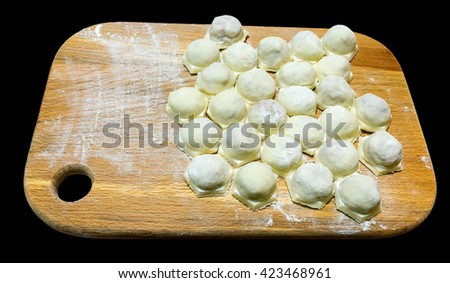 uncooked ravioli ravioli on a wooden board. - stock photo