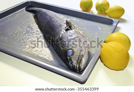 uncooked raw fish ready to be cooked with fresh lemons - stock photo